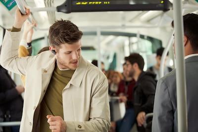 Lifestyle image of man enjoying WF-1000XM3 headphones on public transport.