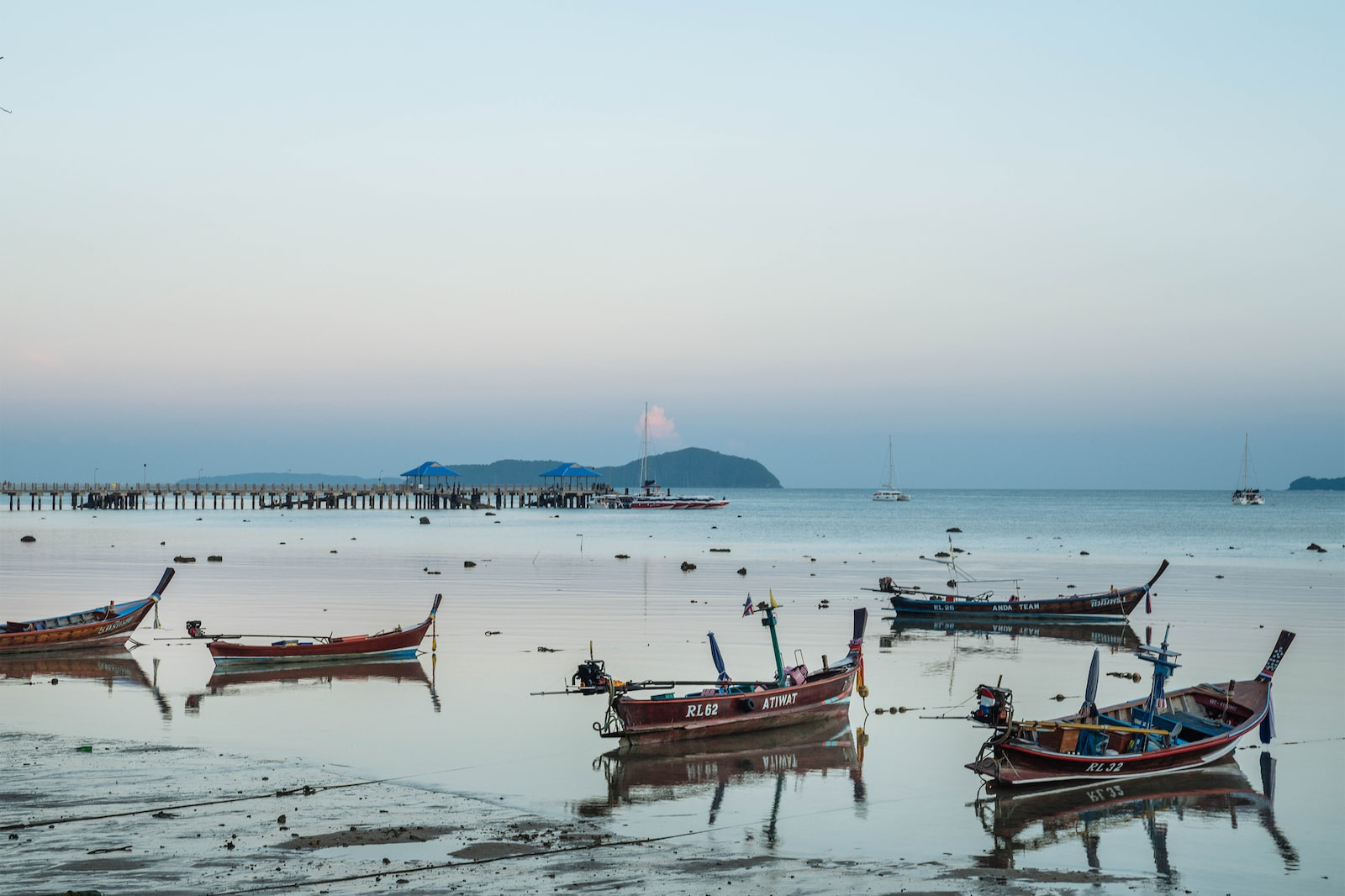 Multiple Sampan boats resting by Phuket sea with island in distance
