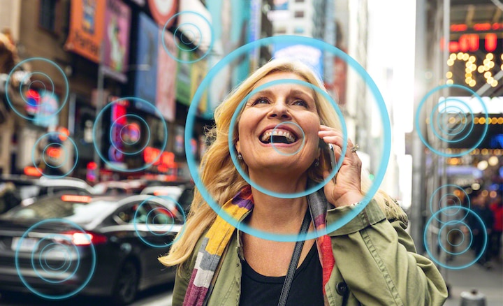 Woman in busy street scene showing how Voice Zoom 2 makes speech easier to hear