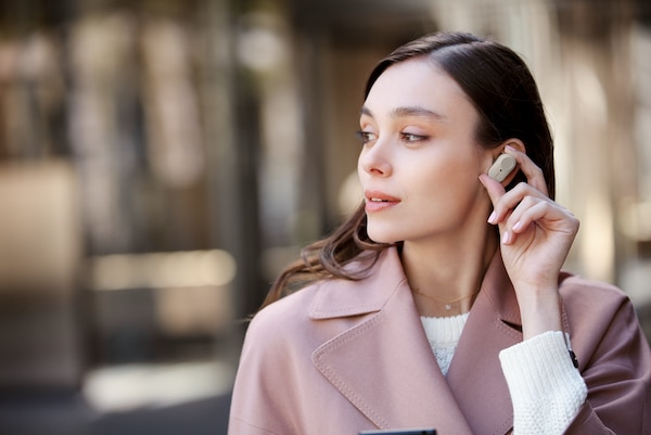 Lifestyle image of woman replacing a WF-1000XM3 earbud in her ear.