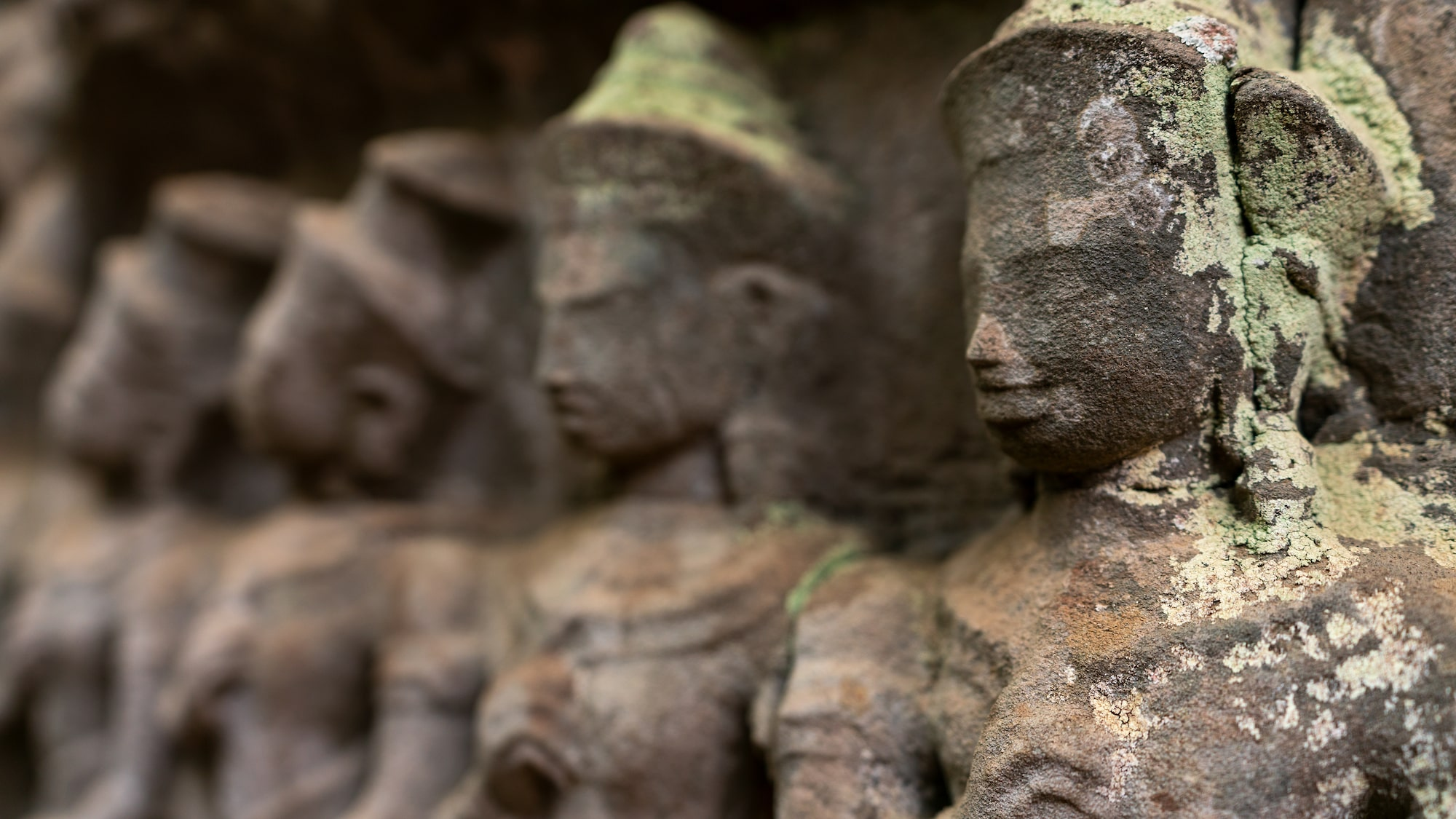 Lineup of stone statues that fades into bokeh in Angkor Wat