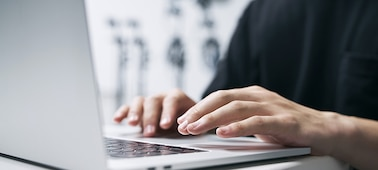 Image of a person typing on a laptop