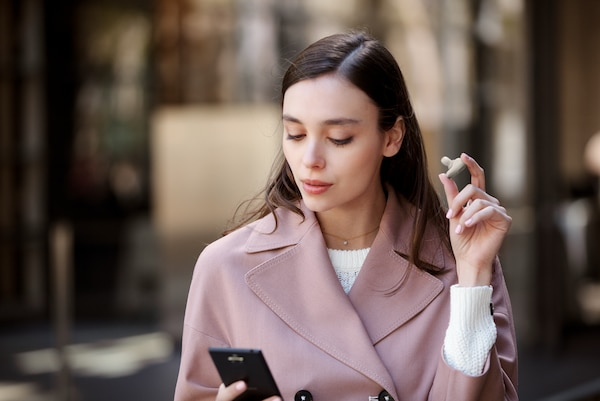 Lifestyle image of woman removing a WF-1000XM3 earbud from her ear.