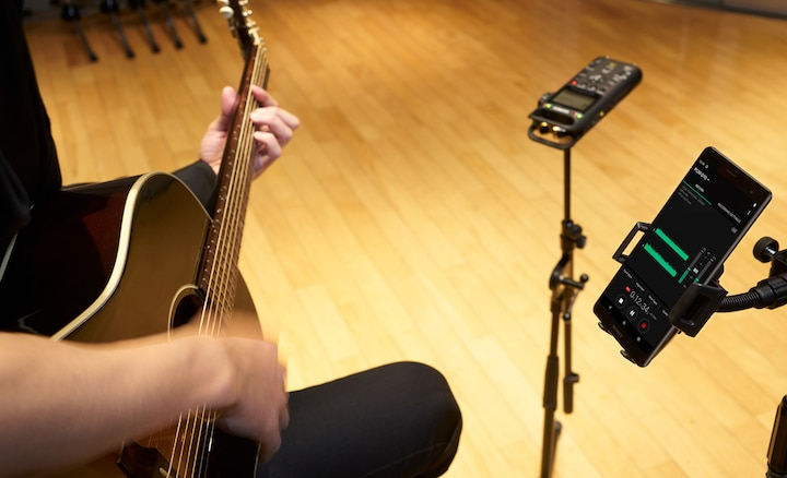 Guitarist plays with the audio recorder fixed to studio stand and a smartphone displaying the REC level in digital view